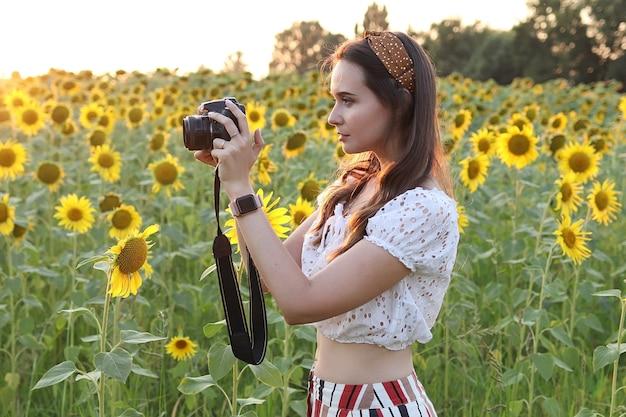 女性写真家は自然の中で写真を撮り、写真家は日没時にひまわりの美しい畑の写真を撮ります。高品質の写真