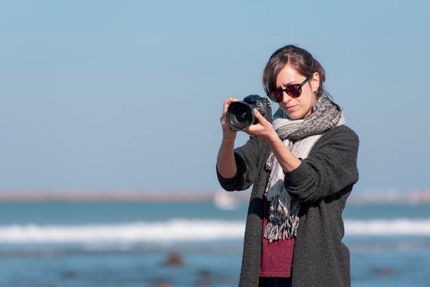 해변에서 사진을 찍는 여성 사진사