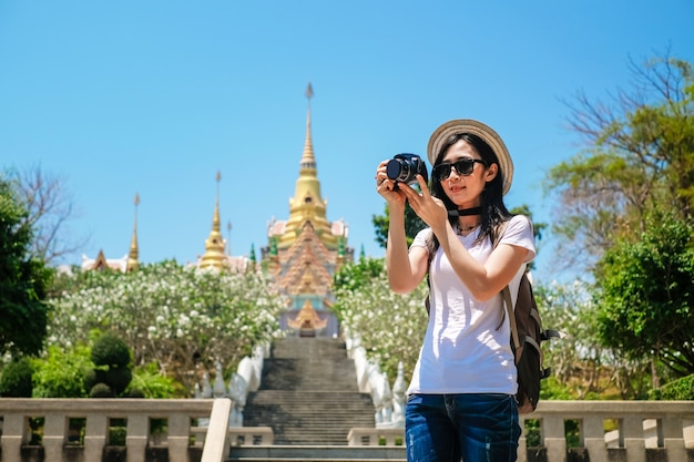 Woman photographer taking photo the temple during travel on holiday