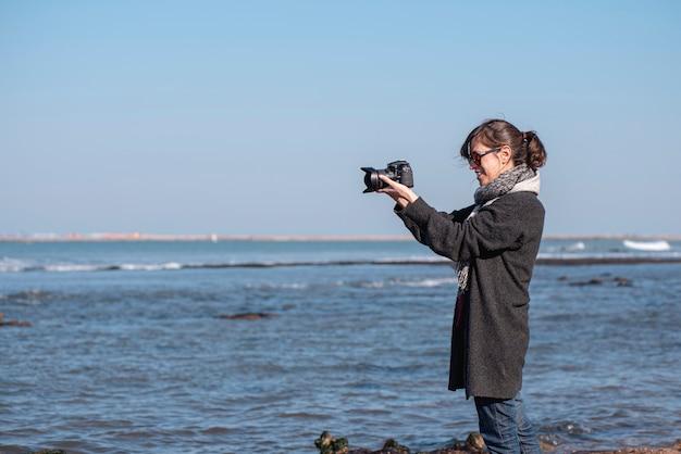 해안에서 사진을 찍는 여성 사진사