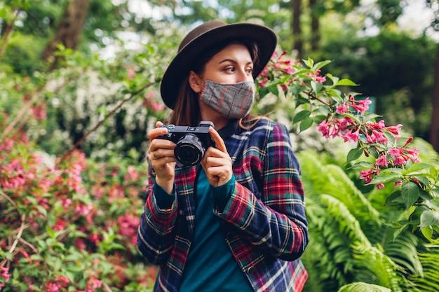 Женщина-фотограф фотографирует на цифровой фотоаппарат в летнем саду в маске. фрилансер любит снимать цветущие растения