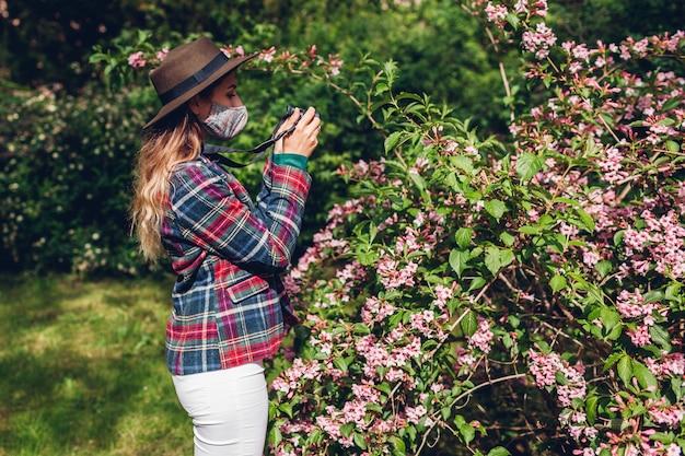 Женщина-фотограф фотографирует с помощью камеры в летнем саду в маске. фрилансер гуляет по парку и снимает цветущие кусты