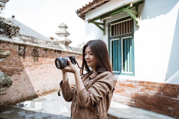Woman photographer taking picture using camera