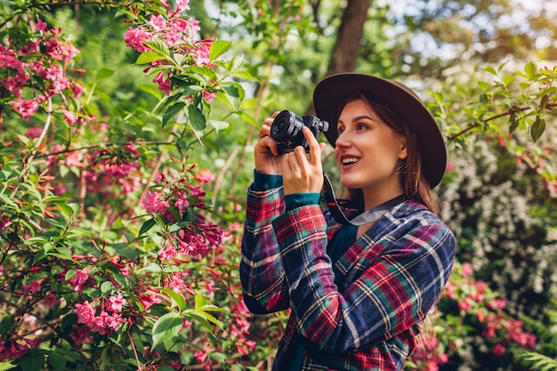 Woman photographer taking pictures using camera in summer garden shooting trees in blossom. freelancer walking in park filming flowers blooming bushes. hobby