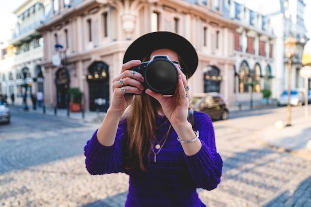 Фотограф женщины фотографируя используя камеру dslr во время гулять вокруг европейского города