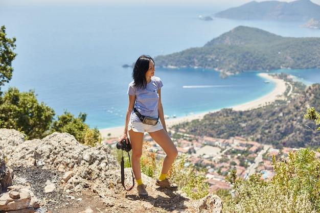 Женщина-фотограф идет по тропе ликийского пути. фетхие, олюдениз. прекрасный вид на море и пляж. поход в горы турции