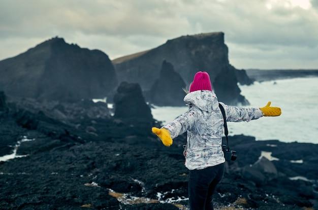 女性写真家は、曇りの天気で黒い火山砂と海岸の素晴らしい海の景色を楽しみながら歩きます。