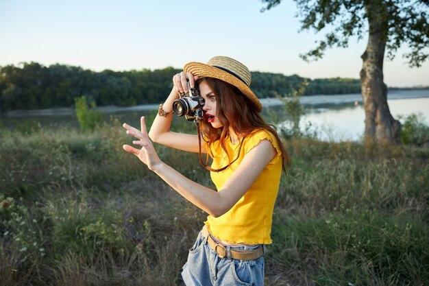 カメラで帽子をかぶっている女性写真家が自然の写真を撮る