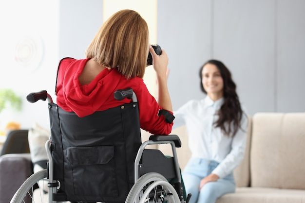 Woman photographer in wheelchair photographs model in photo studio close-up. social adaptation of disabled people concept.