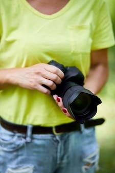 Женщина-фотограф с фотоаппаратом в руке на открытом воздухе