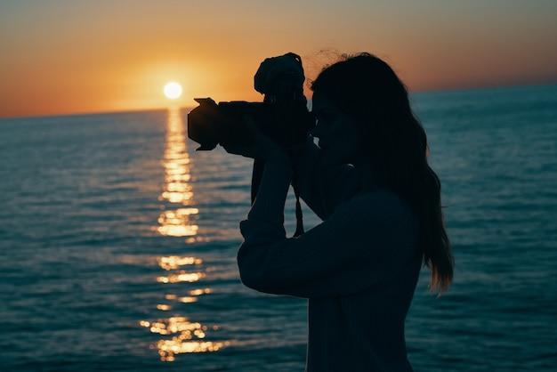 海の自然の風景の近くで日没時にカメラを持つ女性写真家