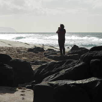 Woman photographing on the beach, haleiwa, north shore, oahu, hawaii, usa