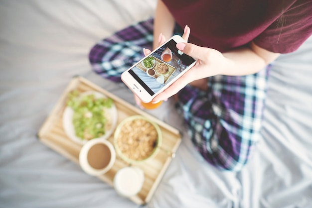 침대에서 아침 식사를 촬영하는 여자