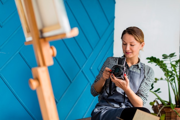 Woman photographing canvas on easel
