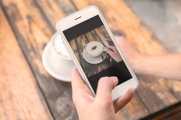 Woman photographing cup of coffee with cell phone