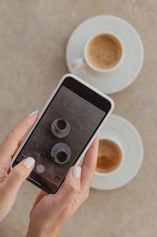 Женщина фотографирует чашки кофе на смартфоне