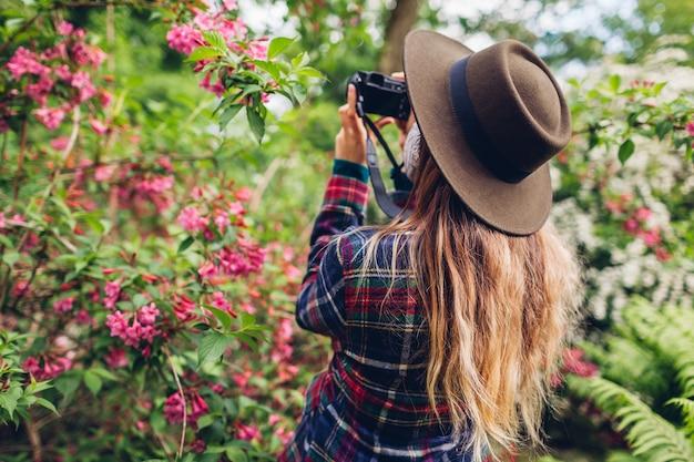 Женщина фотографирует цветы на цифровой фотоаппарат в летнем саду. девушка гуляет, наслаждаясь хобби на открытом воздухе, снимая цветущие кусты