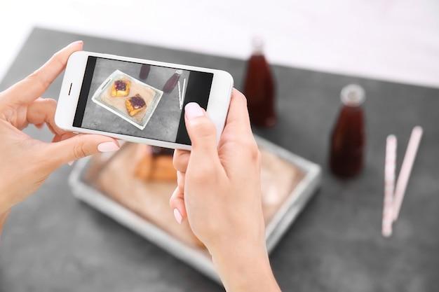 スマートフォンで食べ物を撮影する女性