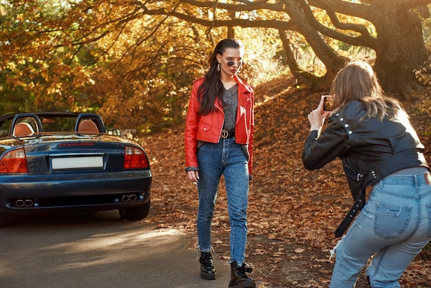 Woman photographing her friend in red coat and sunglasses near cabriolet