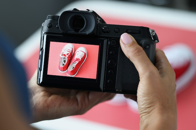 Woman photographing red sports shoes on professional camera closeup