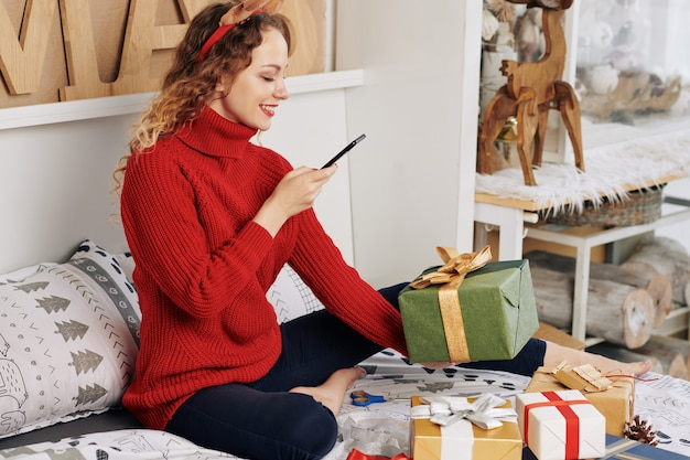Woman photographing wrapped present
