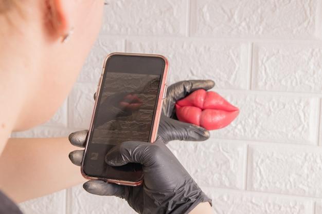 여자는 그녀의 전화로 매 스틱 입술 사진