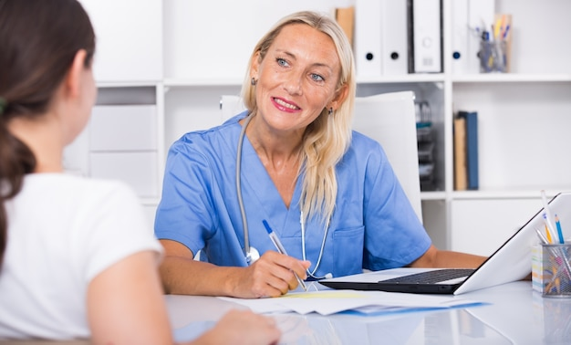 Woman physician consulting female in office