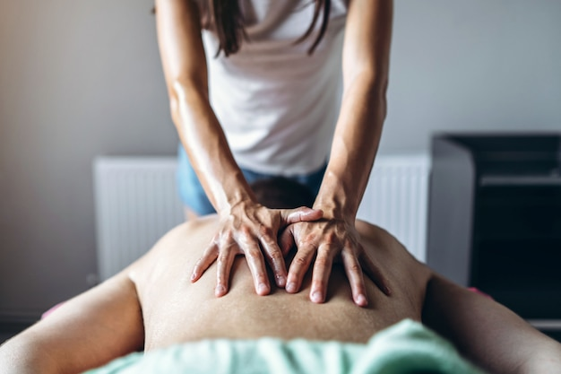 A woman physiotherapist doing back massage for a man in the medical office.