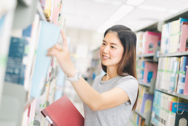 Woman pick a book from the bookshelf in library.