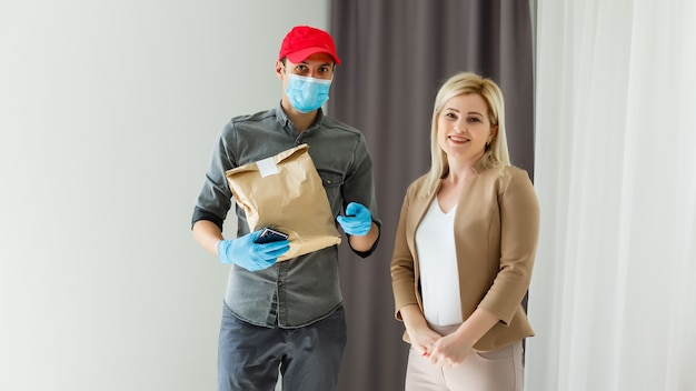 Женщина забирает пакет с доставкой из коробки с доставкой на дом для социального дистанцирования из-за риска заражения.