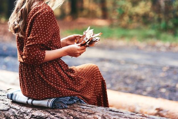 Женщина собирает осенние листья в лесу
