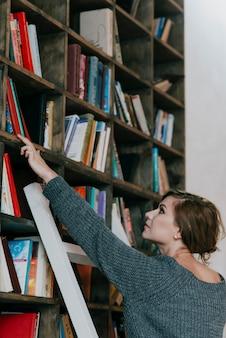 書棚から女性を選ぶ女性