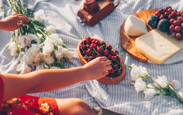 Woman picking up cherries from wooden plate with flowers, cheese and fruits on
