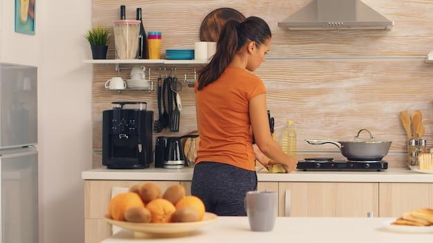 아침 식사를 요리하기 위해 냉장고에서 계란을 줍는 여자. . 주부는 부엌에 있는 냉장고에서 건강한 계란과 다른 재료를 얻고 있습니다.