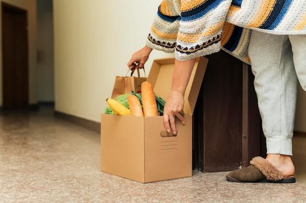Donna che prende la sua spesa in quarantena