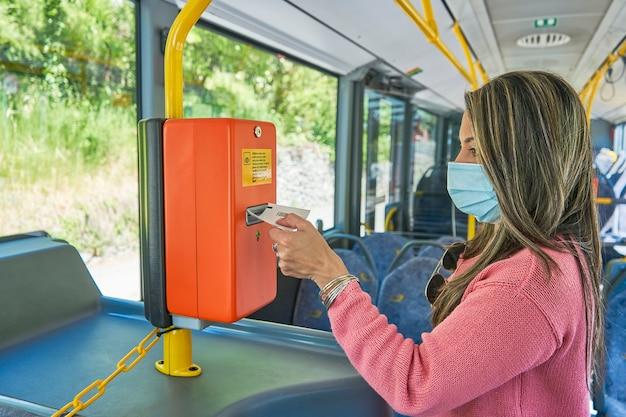 バスの支払い機からチケットを拾う女性のクローズアップ