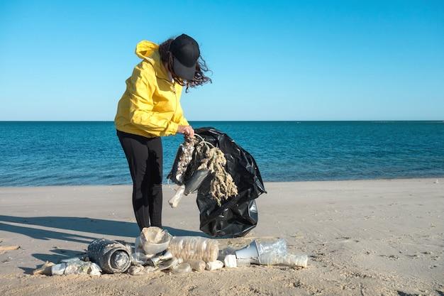 Женщина собирает мусор и пластмассу чистит пляж мешком для мусора. активист-волонтер-эколог против изменения климата и загрязнения океанов.