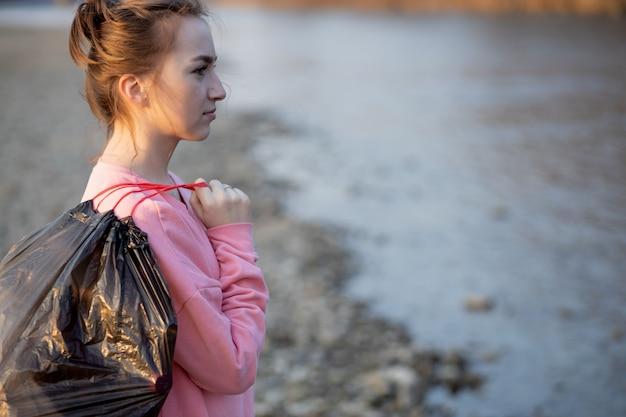 Женщина собирает мусор и пластмассы, чистит пляж с мешком для мусора