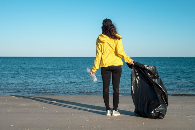 Woman picking up trash and plastics cleaning the beach with a garbage bag. environmental volunteer activist against climate change and the pollution of the oceans.