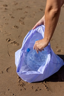 Woman picking up trash and plastics cleaning the beach