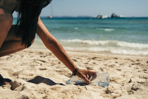 Woman picking up a water bottle garbage from the beach.