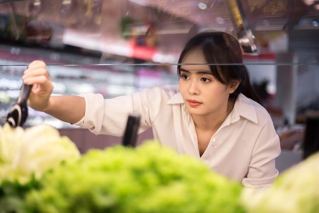 食料品店の棚で野菜を選ぶ女性