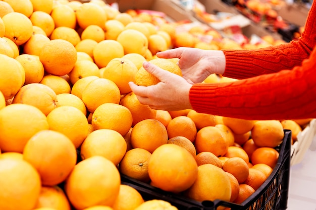 Woman picks juicy oranges in a supermarket. healthy lifestyle and vitamins. close-up.