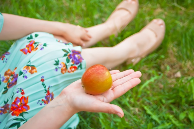 Woman on the picnic sits on the green grass and holds apple in a hand.