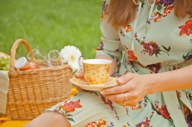 Woman on the picnic sits on the yellow cover and holds cup of tea or coffee.