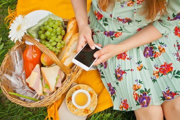 Woman on the picnic sits on the yellow cover and holds phone.