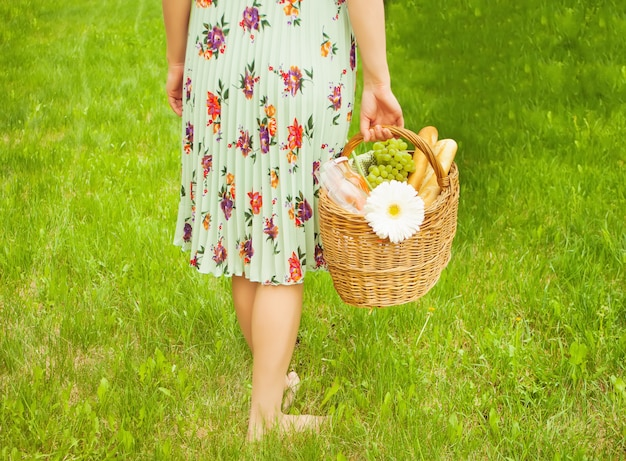 Woman on the picnic stand on the green grass and holds picnic basket in a hand.