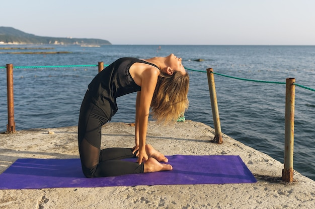 A woman on a pier on a sunny summer evening performs the ushtrasana exercise camel pose
