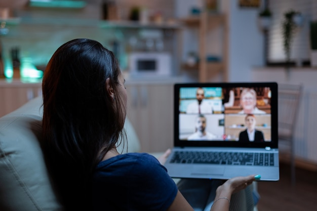 Woman in pijamas lying on sofa using laptop talking about sale report in video conference with team. remote worker having online meeting consulting with colleagues using videocall and webcam chat