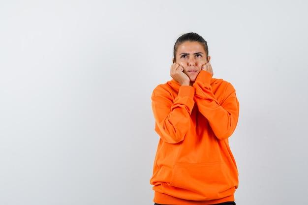 Donna che si appoggia il viso sulle mani con una felpa con cappuccio arancione e sembra pensierosa